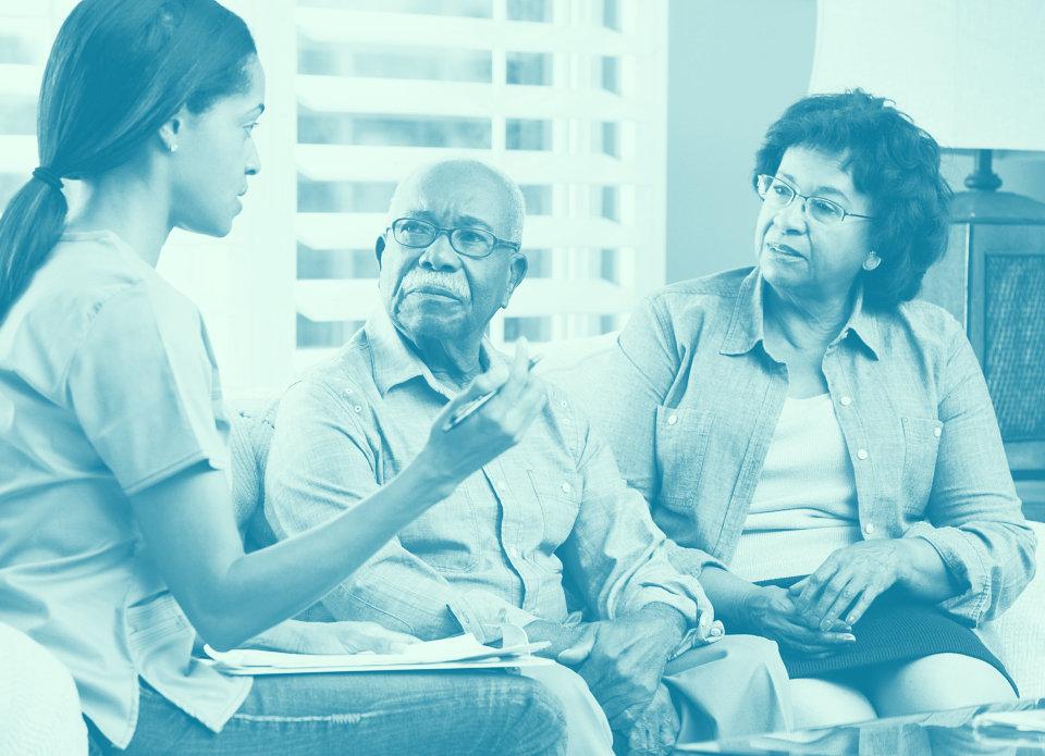 caregiver having a conversation with a senior couple