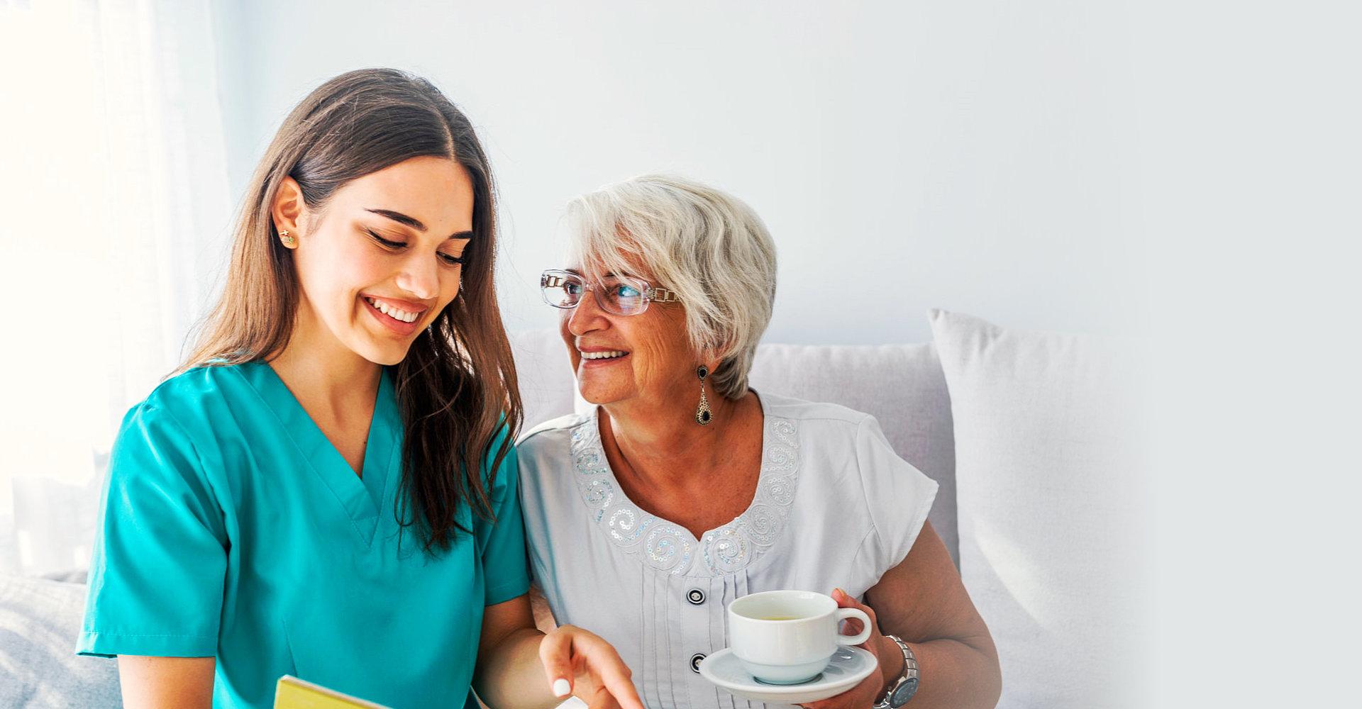 caregiver and a senior woman smiling