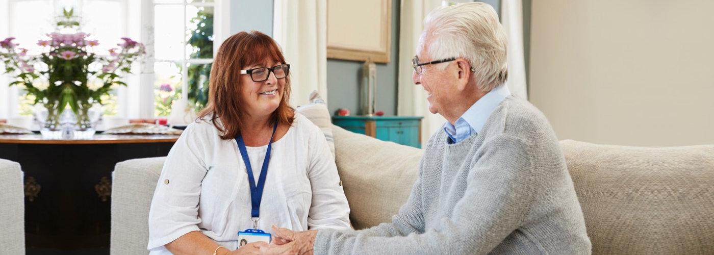 caregiver and a senior man having a conversation